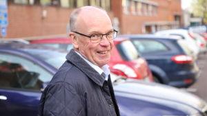 En leende äldre man utomhus. Han har glasögon och blå jacka och många bilar i bakgrunden.