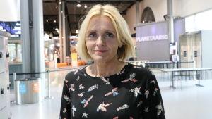 Kvinna i medelåldern med blont hår tittar in i kameran.