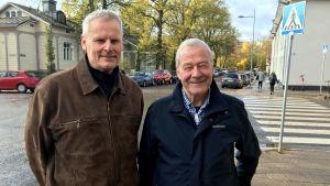 två äldre herrar står på en gata i studentkvarteren i Åbo i höstväder