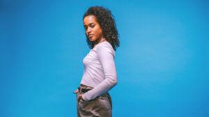 Kiharahiuksinen nainen katsoo suoraan kameraan. Hänellä on päällään valkoinen paita ja vaaleanruskeat housut. Kuvan tausta on sininen.