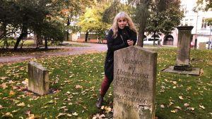 Stina Wollter står lutad över en gravsten i Petsparken