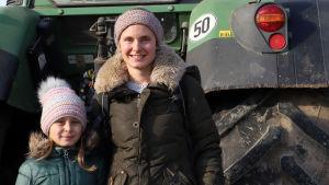 Katarina Stahl med sin dotter framför en traktor.