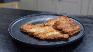 Juustopaneroitu porsaankyljys lautasella