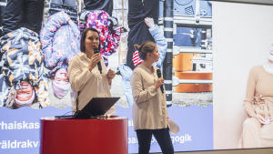 Två kvinnor håller ett föredrag framför en skärm. De ser ivriga ut. På skärmen syns bilder på barn som leker.