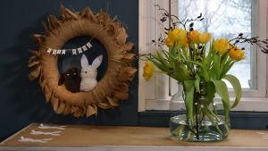 Påskkrans, påskduk och tulpaner vid ett fönster