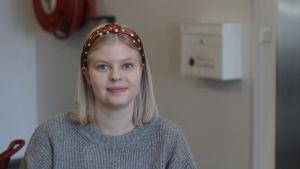 En ung, vit kvinna med blont hår ler mot kameran.