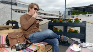 En ung man sitter på ett café i centrala Helsingfors och slukar en smörgås. Framför sig har han en kaffekopp och på bänken ligger han sin läderväska och en kamera,