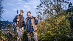 Evelina och Peter i en skogsdunge med gevär i händerna.