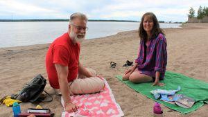 En man och en kvinna sitter på var sin badhandduk på en sandstrand.