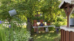 Krukor är målade och ihopsatta så de ser ut som en pojke och en flicka. Krukbarnen sitter på en bänk mellan två buskar. Till höger finns en röd brunn och till vänster en vattenkanna som ser ut att sväva i luften.