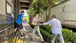 Personal på KInas konsulat i Houston lassar in skyddsutrustning för covid-19 i april 2020.