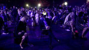 En grupp mötesdeltagare med munskydd sitter glest i blått upplyst mötessal.