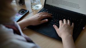 En person skriver på en laptop.