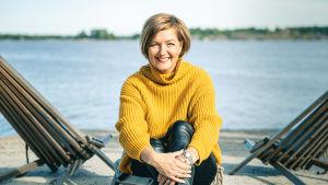 Maria Sundblom Lindberg sitter på en brygga med vattnet i bakgrunden och tittar rakt in i kameran.