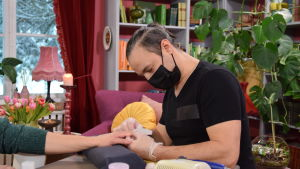 Alexey Kriventsov inspekterar Nicke Aldéns hand med ett svart munskydd på sig.
