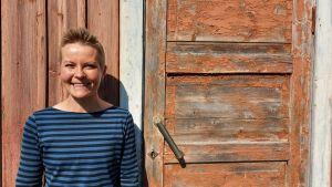 saarela står lutad mot en gammal trävägg, bredvid en gammal dörr i övergivet hus.hon ler
