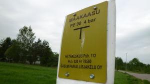 En skylt som visar var en naturgasledning går. Gul skylt, svart text.