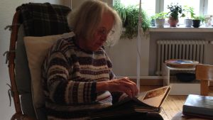 Chris-May Savonius bläddrar i gamla fotoalbum efter fiskeminnen.