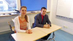 Bild på två personer som sitter i ett klassrum.