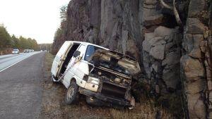 En krockad skåpbil vid en bergsvägg.