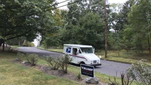 En postibi. kör förbi en Trumpskylt i New Jersey i USA:
