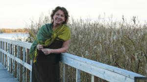 ekofrisörutbildaren mona mether står vid havet lutad mot ett brostaket med vass i bakgrunden i en grön skarf och svart klänning