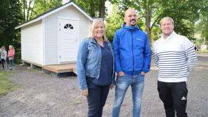 Elisabet Ehrstedt, Matias Kaihovirta och Henrik Lagerbohm på Katarinaskolans gård med nya redskapshuset i bakgrunden.