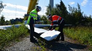 Jyrki Rajala från Vasa Elektriska och Janne Salonen från Delete inspekterar propellern från en av möllorna i Korsnäs.