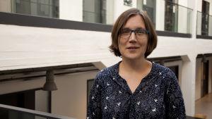 Blanka Henriksson står i en universitetsmiljö. Hon bär en mörkblå blus eller klänning och har glasögon.