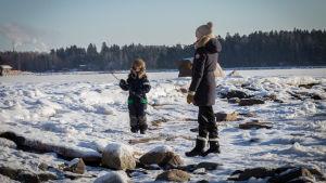 Sääkuva Espoosta Haukilahden rannasta, pakkasta yli -10, meri jäässä, kuvassa äiti Mari Mannila Haukilahdesta ja lapsi Olli, 7.2.2017.