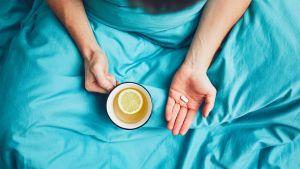 Symbolisk bild för förkylning. En person sitter i sängen med en kopp te och en huvudvärkstablett.