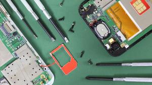 Två trasiga mobiltelefoner med mikrochipen framme, små skruvmejslar på grönt underlag