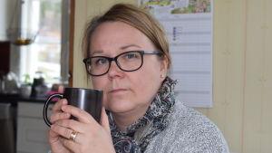 Christel Lindqvist-Jauhiainen sitter i sitt kök med kaffemugg i handen. Allvarlig, ler inte.