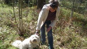 En kvinna som håller i ett koppel som går till en vit hund. Kvinnan böjer sig ner lite och tittar på hunden.