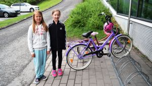 Två barn vid sina cyklar utanför Prisma i Lojo.