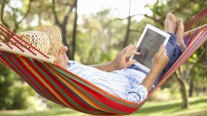 En äldre man ligger i en hängmatta och läser på en läsplatta.