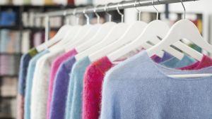 Olika färgers ylleplagg hänger i radpå en klädställning