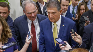 Joe Manchin omringad av journalister.