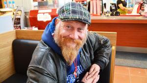 En man med skägg tittar in i kameran med ett spjuveraktigt leende.