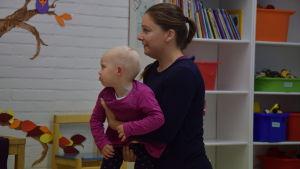 En kvinna står med ett barn i famnen. Hon deltar i en musiklek.