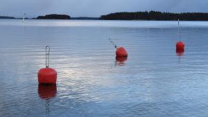 Tre rödorangea bojar i ett blåskimrande hav.