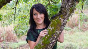 Tuhkimotarinoiden ohjaaja Mape Morottaja pitää kiinni omenapuun rungosta ja katsoo hymyillen kameraan vihreässä mekossa.