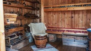 Inuti en liten stuga i trä: våningssäng, hyllor med verktyg, skinnfällbeklädd stol gjord av en gammal tunna.