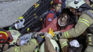 Räddningsmanskap bär ut en skadad kvinna från rasmassorna efter att ett flervåningshus rasade i Istanbul,.