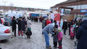Två lastbilar står på torget i Kristinestad. Runt lastbilarna står abiturienter som firar sin penkisdag. Även intresserade Kristinestadsbor står samlade på torget.