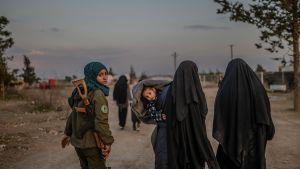 Två hustrur till IS-krigare går längs en väg. Bredvid dem går en kvinnlig kurdisk soldat.