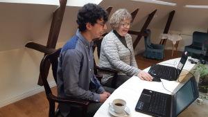 en ung mörkhårig man sitter på gammaldags stol bredvid en äldre medelålders kvinna. Framför sig på bordet har de två datorer, en grönväxt och en kaffekopp
