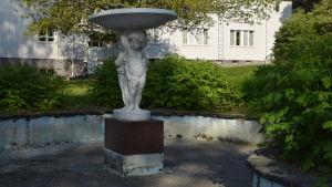 En skulptur i marmor som föreställer två pojkar som håller upp ett kärl. Skulpturen finns i enn torrlagd bassäng.