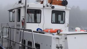 Ett vitt forskningsfartyg förtöjt vid en brygga. Man ser inte hela fartyget. Dimma.