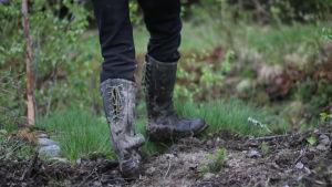 Leriga stövlar vandrar i skogen.